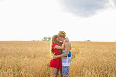 Young couple kissing in a field. Young woman hugging a caucasian man in the middle of a wheat field and kissing each Royalty Free Stock Photo