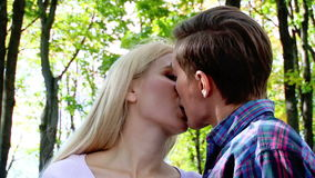 Young couple kissing and flirting in  park. Close up of young couple kissing  in  park. Shooting with a tripod. Retreat camera stock footage
