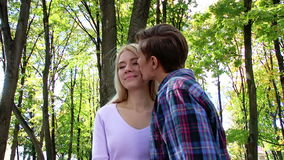 Young couple kissing and flirting in  park. Young loving couple kissing  in  park. Used steadicam stock footage