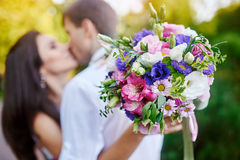 Young couple kissing and a girl holding a beautiful bouquet Royalty Free Stock Photo