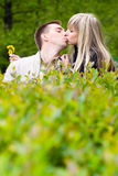 Young couple kissing in green bushes Royalty Free Stock Images