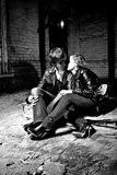 Young couple kissing on ground at abandoned building Stock Images