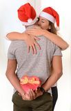 Young Couple kissing and hidden Christmas Present Royalty Free Stock Photo