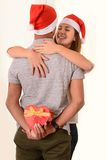 Young Couple kissing and hidden Christmas Present Stock Photography
