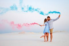 Young couple kissing and holding colored smoke in hands, romantic couple with blue color and red color smoke bomb on beach stock photo