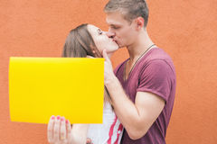 Young couple kissing and holding frame at background of wall Stock Photography
