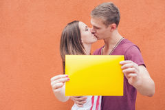 Young couple kissing and holding frame at background of wall Stock Photos