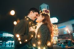 Young couple kissing and hugging outdoor in night street at christmas time stock photos