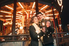 Young couple kissing and hugging outdoor in night street at christmas time royalty free stock photography