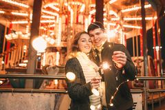 Young couple kissing and hugging outdoor in night street at christmas time. At city stock photo