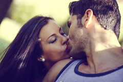 Young Couple Kissing In A Beautiful Park Royalty Free Stock Photos