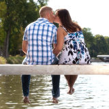 Young couple kissing on lake pier Royalty Free Stock Images