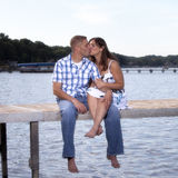 Young couple kissing on lake pier Stock Images