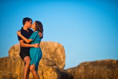 Young couple kissing in the middle of rocks under the blue sky. Beautiful young couple kissing in the middle of rocks under the blue sky Stock Photo