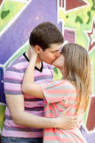 Young couple kissing near graffiti background. Stock Images