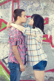 Young couple kissing near graffiti background. Royalty Free Stock Image