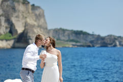 Young couple kissing near sea in wedding day in Naples. Italy Stock Photography