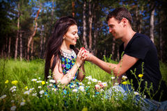 Young couple kissing outdoor in summer sun light. Kiss love date color evening teen. Young couple in the woods royalty free stock photos