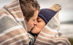 Young couple kissing outdoors under blanket in a Royalty Free Stock Photo