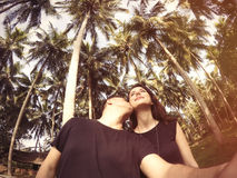 Young couple kissing. On palms background Royalty Free Stock Photos