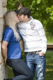 Young Couple Kissing in Park. Young couple in the park leaning against a stone wall kissing royalty free stock image