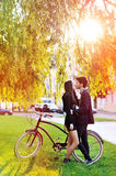 Young couple kissing in a park near a vintage bike Royalty Free Stock Image