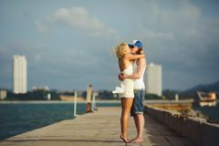 Young couple kissing on the pier against the sea. honeymoon lovers. Stock Photos