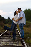 Young couple kissing on rail tracks Royalty Free Stock Photography