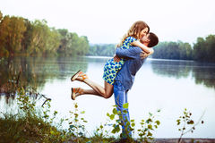 Young couple kissing and rejoices at the lake. A loving couple hugging and kissing by the lake. The girl picks up a guy in the air Royalty Free Stock Photography