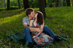 Young couple kissing on a romantic picnic. In a park on a sunny day outdoors Royalty Free Stock Images