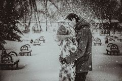 Young couple kissing on snow. Black and white. Royalty Free Stock Image
