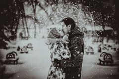 Young couple kissing on snow. Black and white. Royalty Free Stock Images