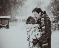 Young couple kissing on snow. Black and white. Stock Images