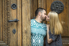 Young couple kissing while standing next to an ancient doors. Royalty Free Stock Images