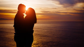 Young couple kissing on sunset towards the sea Royalty Free Stock Images