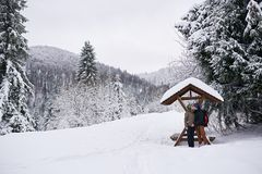 Young couple kissing under a shelter while hiking in winter royalty free stock photography