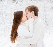 Young couple kissing in winter forest.  Stock Photo