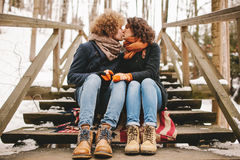 Young couple kissing on wooden stairs outdoors in winter Stock Photo