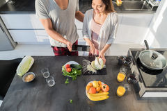 Young Couple In Kitchen, Asian Woman Cooking Food Breakfast, Hispanic Man Show Cell Smart Phone. Modern Apartment Interior Stock Photo