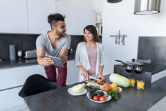 Young Couple In Kitchen, Asian Woman Cooking Food Breakfast, Hispanic Man Show Tablet Computer Stock Image