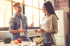 Young couple in kitchen. Beautiful young couple is talking, looking at camera and smiling while cooking in kitchen at home. Woman is mixing salad stock photos