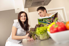 Young couple in kitchen choosing recipe. From cookbook drinking red wine Royalty Free Stock Image