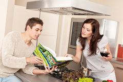 Young couple in kitchen with cookbook Stock Image