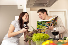Young couple in kitchen with cookbook Stock Images