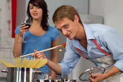 Young couple in the kitchen cooking dinner Stock Photos