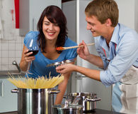 Young couple in the kitchen cooking dinner Stock Photo