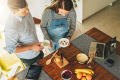 Young couple in kitchen cooking. Man is standing near table and drinking tea, his pregnant wife is standing next to him Royalty Free Stock Photography
