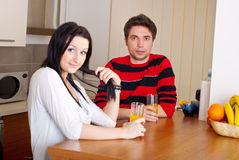 Young couple in kitchen drink juice Royalty Free Stock Photography