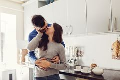Young couple in the kitchen hugging and kissing stock images