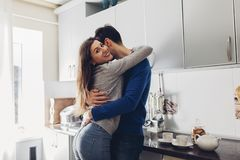 Young couple in the kitchen hugging and making tea stock image